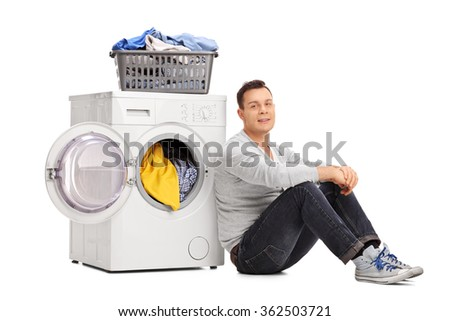 Young man sitting by a washing machine and looking at the camera isolated on white background - stock photo