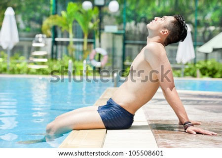 Young man sitting by swimming pool and taking a tan