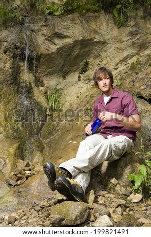 Young man sitting by waterfall, looking away