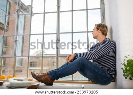 Young man sitting daydreaming on the windowsill of a large view window in his apartment overlooking an urban street - stock photo