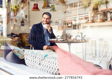 Young man sitting in a cafe - stock photo