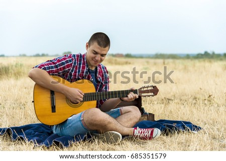 Young man sitting in a field and playing acoustic guitar