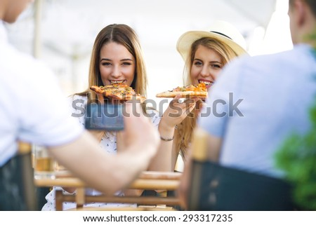 Young man sitting in a restaurant with his friends photographing two girls eating pizza