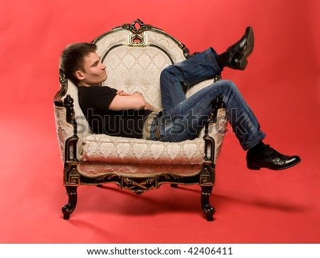 young man sitting in antique armchair - stock photo