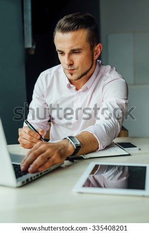 Young man sitting in cafe and adding new meeting in his calendar. Indoor photo