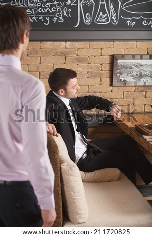 young man sitting in cafe waiting for somebody. handsome guy looking at his handwatches while waiter standing near - stock photo