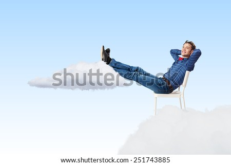 Young man sitting in chair with legs up and relaxing - stock photo