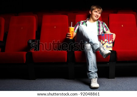 Young man sitting in cinema and watching movie