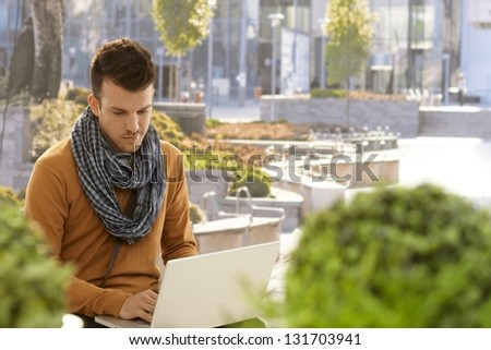 Young man sitting in citypark, using laptop computer. - stock photo