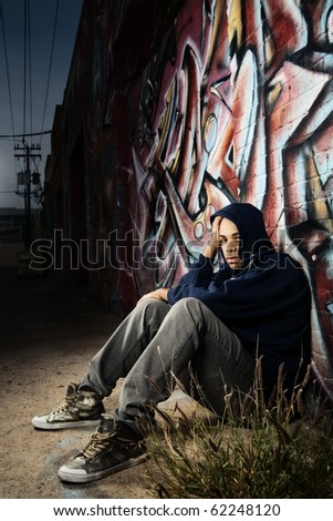 Young man sitting in dark alley against a graffiti wall