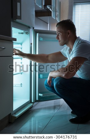 Young Man Sitting In Front Of Empty Fridge At Nighttime
