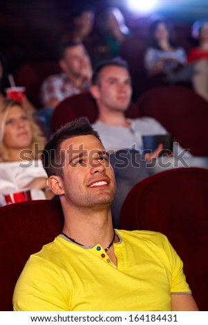 Young man sitting in multiplex movie theater, watching movie, smiling. - stock photo