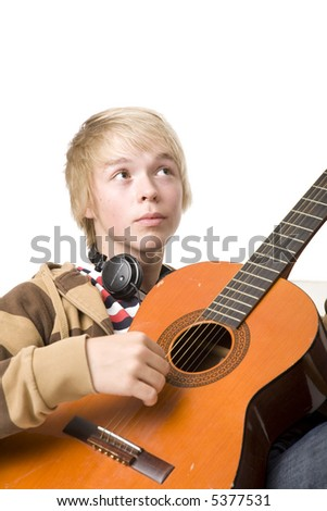 Young man sitting in sofa and playing an acoustic guitar - stock photo