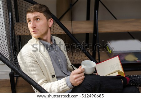 Young man sitting in the armchair with a cup of coffee and a book is looking up