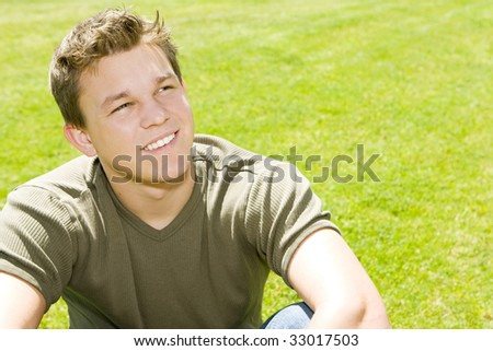 Young man sitting in the grass - stock photo