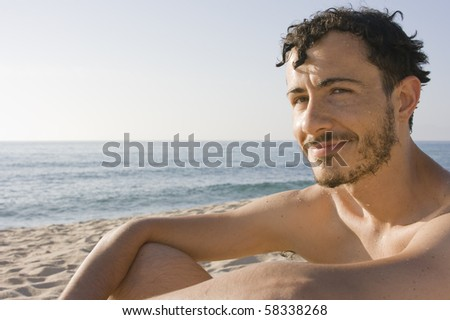 young man sitting in the sand of a beach on Sardinia, Italy - stock photo
