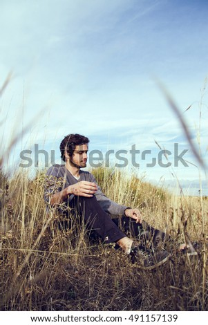 Young man sitting in  wild fields