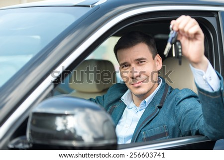 Young man sitting inside new car and showing keys to it. Concept for car rental
