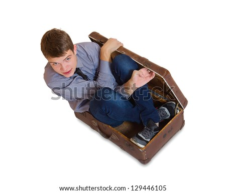 Young man sitting inside old brown suitcase - stock photo