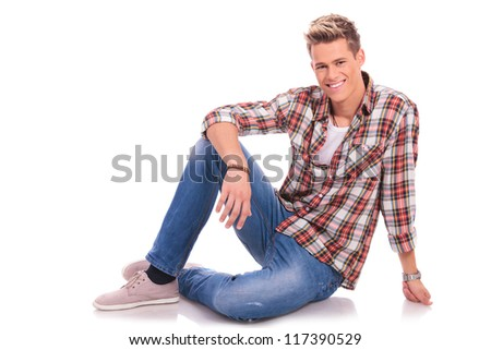 young man sitting/laying on the floor and smiling to the camera, on white background - stock photo