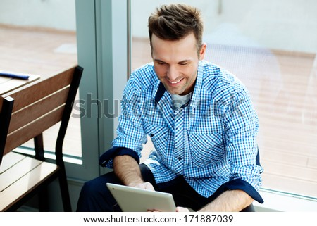 Young man sitting next to a window and using his tablet - stock photo
