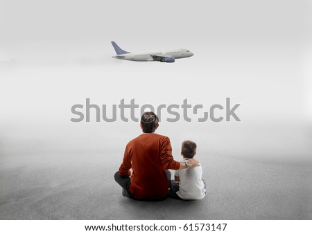 Young man sitting next to his son with airplane on the background - stock photo