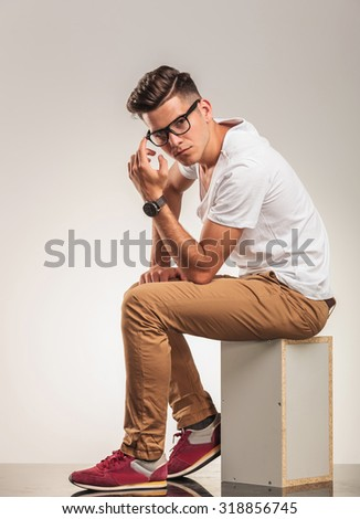 young man sitting on a chair thinking and looking at the camera - stock photo