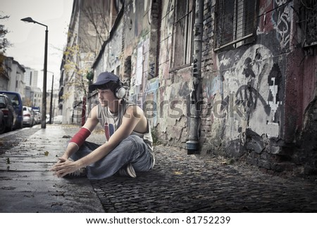 Young man sitting on a city street - stock photo