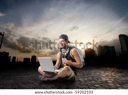 Young man sitting on a city street and using a laptop