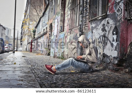 Young man sitting on a city street and using a laptop - stock photo