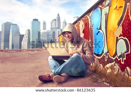 Young man sitting on a city street and using a laptop with graffiti in the background