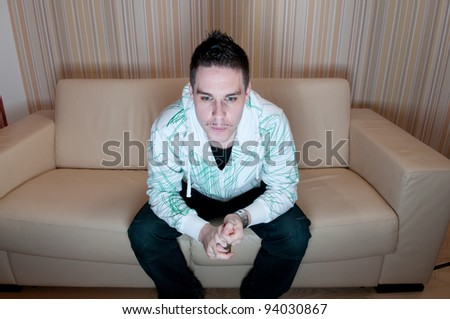 Young man sitting on a couch and watching television - stock photo