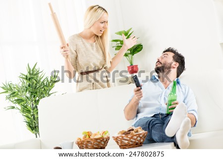 Young man sitting on a couch next to a basket of pastries with his feet up on the table, looks at the woman standing behind him with a rolling pin in her hand and an angry expression on her face. - stock photo