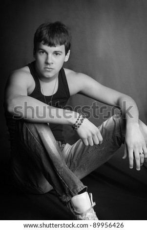 young man sitting on a dark background