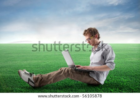 Young man sitting on a green meadow and using a laptop