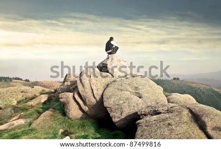 Young man sitting on a hilltop - stock photo