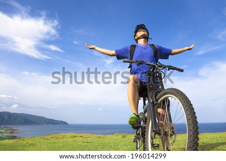 young man sitting on a  mountain bike and open arms to relaxing - stock photo