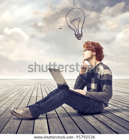 Young man sitting on a parquet floor and using a laptop with light bulb over his head - stock photo