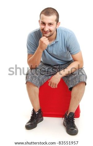 young man sitting on a red cube, isolated on white - stock photo