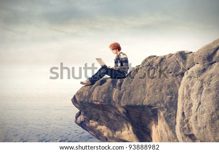 Young man sitting on a rock ad using a laptop - stock photo