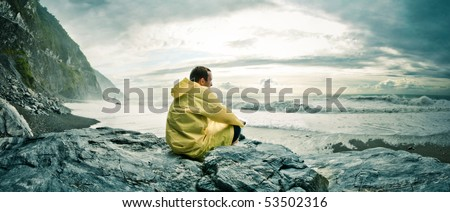Young man sitting on a rock on a rocky beach watching the ocean in a yellow rain coat Location: Hualien County, Taiwan - stock photo