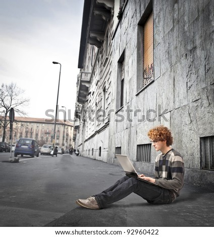 Young man sitting on a sidewalk on a city street and using a laptop - stock photo