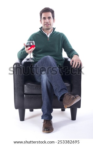 Young man sitting on a sofa and drinking some wine - stock photo