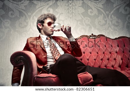 Young man sitting on a sofa and drinking some wine