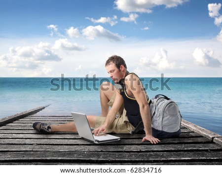 Young man sitting on a wharf and using a laptop - stock photo