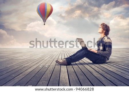 Young man sitting on a wooden floor and using a laptop with hot-air balloon in the background - stock photo