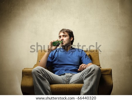 Young man sitting on an armchair and drinking a beer - stock photo