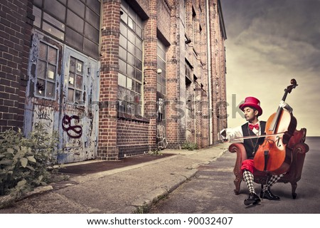 Young man sitting on an armchair on a city street and playing the cello - stock photo