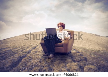 Young man sitting on an armchair on a field and using a laptop - stock photo