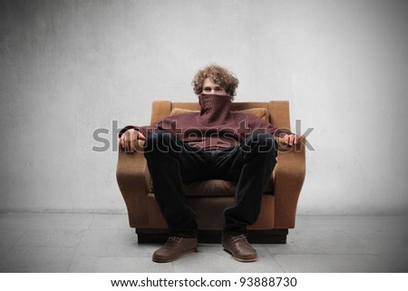 Young man sitting on an armchair with turtleneck sweater on his mouth - stock photo